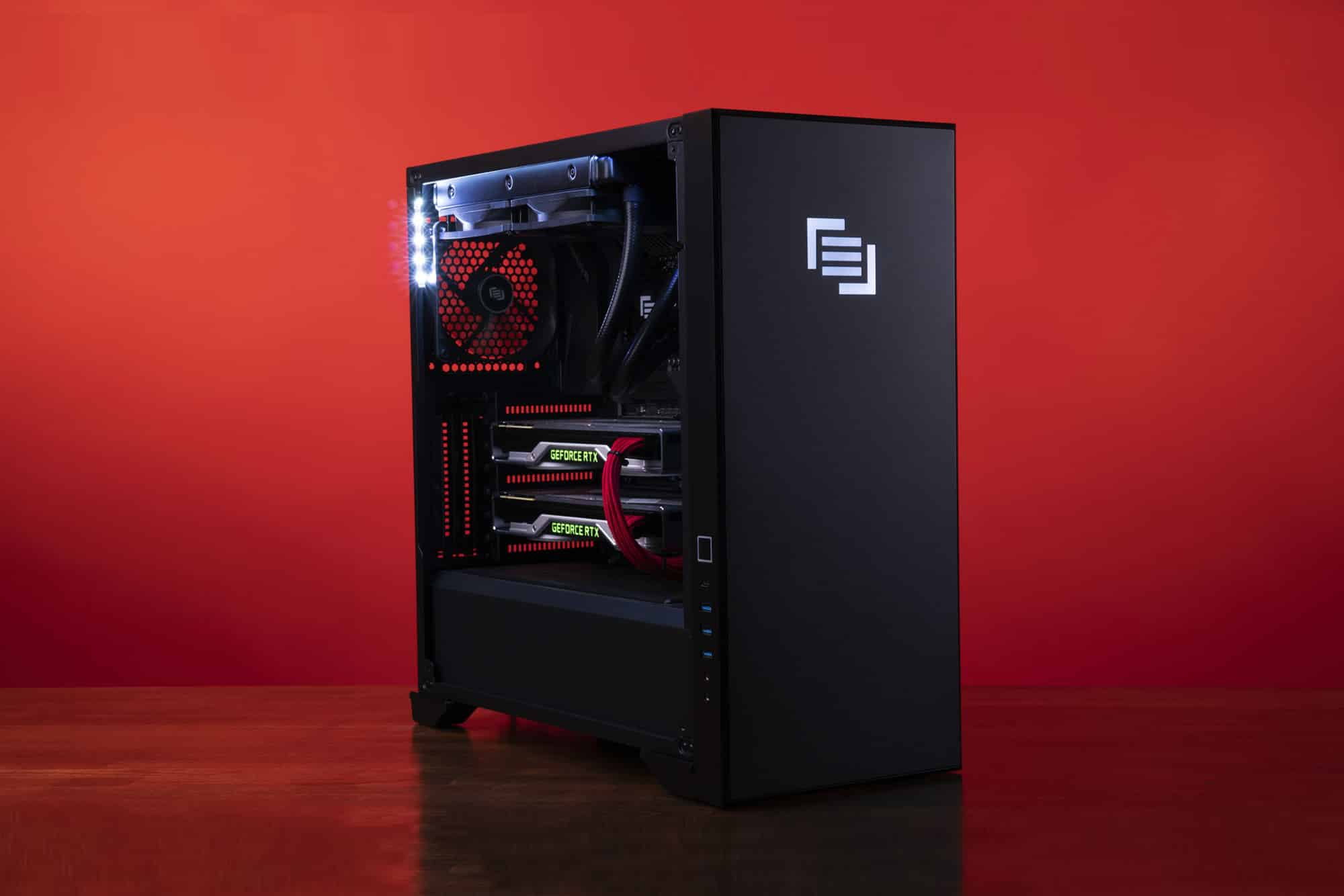 Maingear Vybe Custom PC with dual graphics cards on a wood table with a red background.